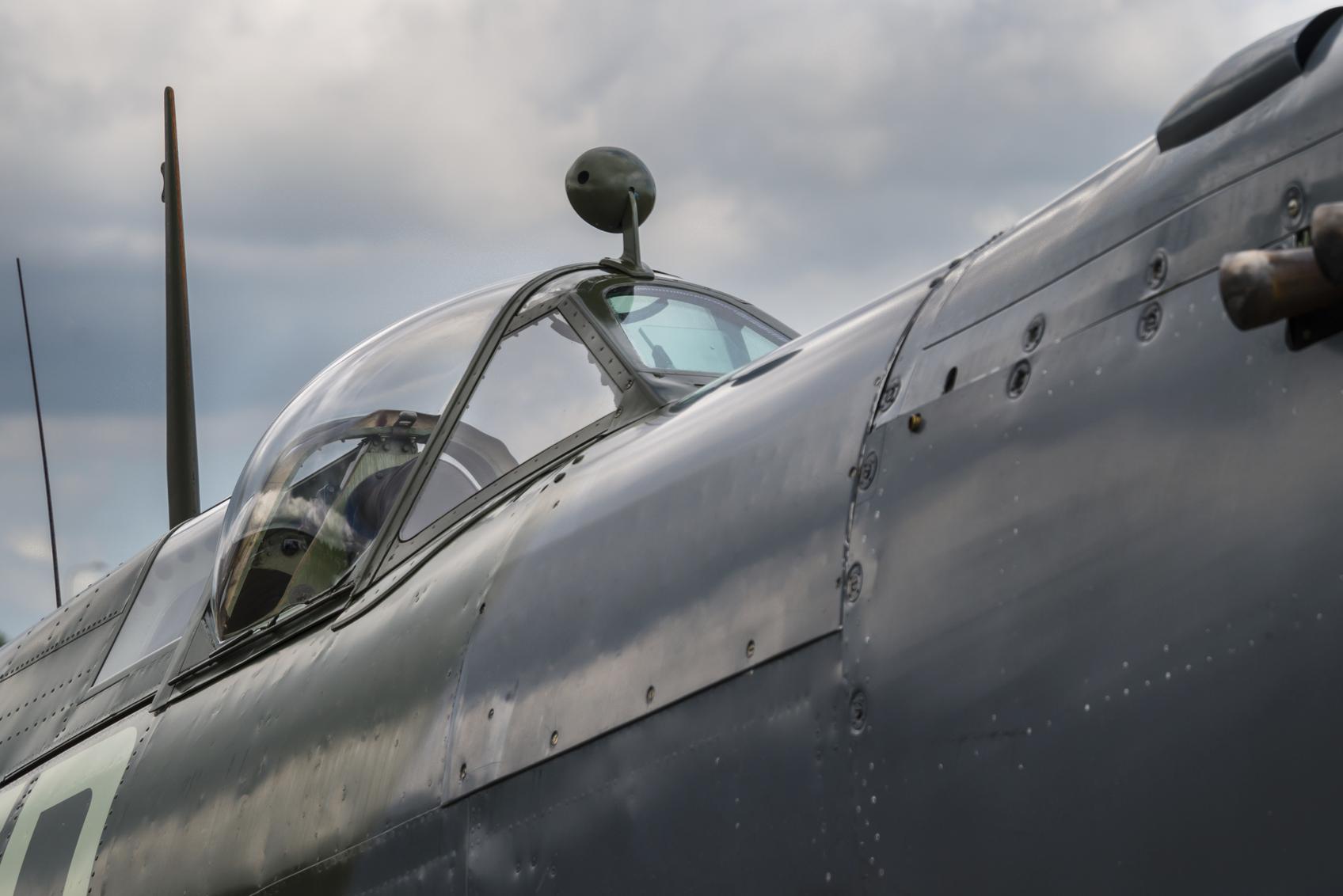 Zpětné zrcátko zvnějšku kokpitu staršího bojového letounu.
