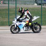 Elektrická motorka na závodní dráze se závodníkem